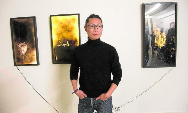 El pintor coreano Kihong Chung, delante de tres de sus obras./LV