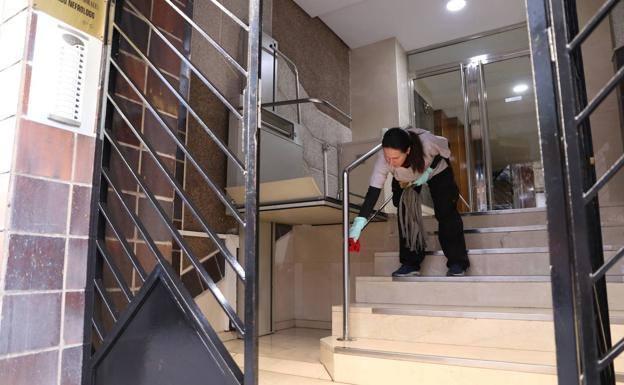Una mujer limpia los pasamanos del portal de un edificio en plena crisis del coronavirus./J.P.