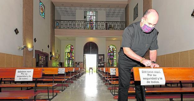 Antonio Carpena, párroco de la Inmaculada en Cartagena, pone distintivos en los bancos. / ANTONIO GIL / AGM
