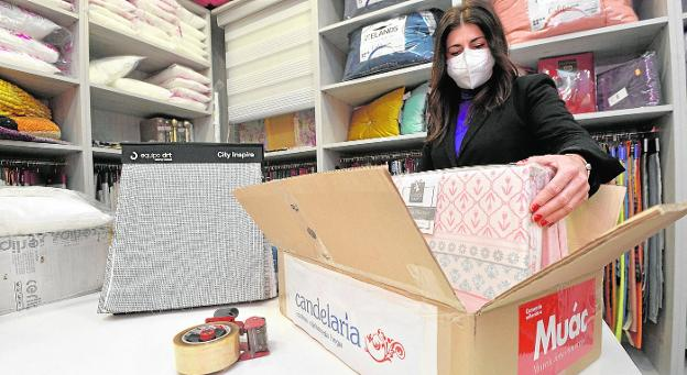 A clerk at the Candelaria Hogar store, in the Vistalegre neighborhood, prepares a home delivery, using a neutral box without labeling with several stickers.