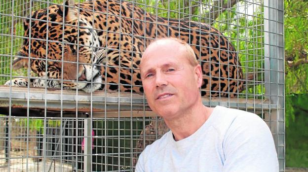 Pedro posa con uno de los jaguares que tiene en un recinto perimetrado y adaptado a las necesidades de los grandes felinos. /