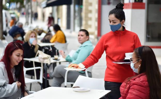 Una camarera de un bar de Alcantarilla atiende a unas clientas en una terraza./Javier Carrión / AGM